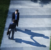 Aerial view of two businessmen shaking hands on the sidewalk Royalty Free Stock Photo