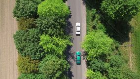 Aerial view two cars of green and white are moving along a narrow road one after the other. Top view.  stock video