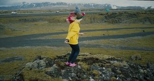 Aerial view of the two happy woman in bright clothes dancing on the top of mountain. Tourist in lava field in Iceland. Aerial view of the two happy woman in stock video