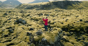 Aerial view of two happy woman standing on the lava field in Iceland and making selfie photo on smartphone. Tourists girls enjoying the beautiful landscape of stock footage