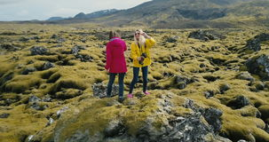 Aerial view of the two happy woman standing on the rock and having fun, dancing. Lava field in Iceland covered moss. Tourists enjoying the beautiful landscape stock video