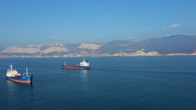 Aerial view of two large cargo ships leaving sea harbour at sunny day