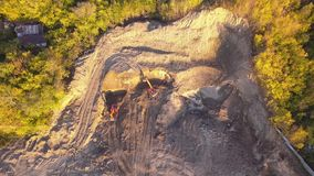 Aerial view of two orange excavators standing at a quarry, one of which extracts soil at the foot of a hill near a construction si stock video