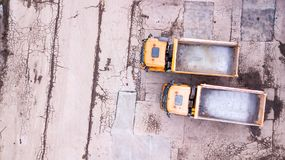 Aerial view of two orange trucks. in front of warehouse. Stock Images