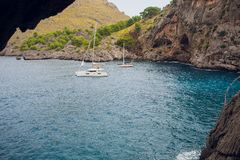 Aerial view of two sailing boats anchoring next to reef. Bird eye view, water sport theme. stock photography