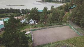 Aerial view of two sports fields for playing football and basketball with players playing in a team located among the high Altai m stock footage