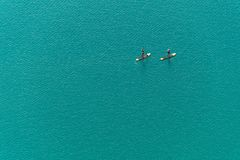 Aerial view of two unidentified stand up paddle boarders on the lake. Aerial view of two unidentified stand up paddle boarders on the turquoise water background Royalty Free Stock Photography