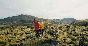 Aerial view of two woman standing on the rock in lava field in Iceland. Tourists looks on landscape, dancing and jumping. Happy girls having fun after hiking stock video footage