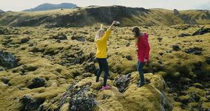 Aerial view of two woman standing on the rock, looking on the lava field in Iceland and dancing, feeling freedom, happy. Aerial view of two woman standing on stock video