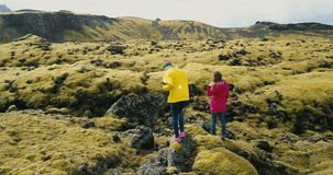 Aerial view of two woman walking on the lava field in Iceland. Tourists exploring the meadow covered moss, hiking. stock footage
