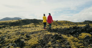 Aerial view of two woman walking on the lava field in Iceland. Tourists female hiking on the mountains covered moss. stock video