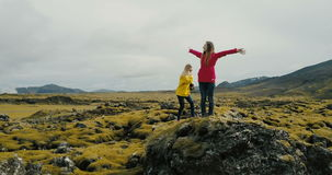 Aerial view of two woman walking on the lava field in Iceland. Tourists hiking on the rocks, feeling freedom and happy. Girls enjoying the beautiful landscape stock video
