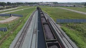 Aerial view UHD 4K of freight train with wagons and standing train with coal. On summer day stock footage