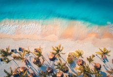 Aerial view of umbrellas, palms on the sandy beach of blue sea. At sunset. Summer travel in Zanzibar, Africa. Tropical landscape with palm trees, parasols stock photography