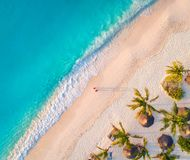 Aerial view of umbrellas, palms on the sandy beach. Of Indian Ocean at sunset. Summer in Zanzibar, Africa. Tropical landscape with palm trees, parasols, walking royalty free stock photos