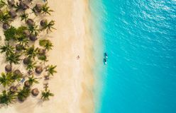 Aerial view of umbrellas, palms on the sandy beach and kayaks. In the sea at sunset. Summer holiday in Zanzibar, Africa. Tropical landscape with palm trees stock image
