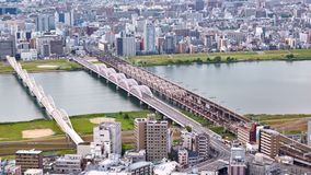 Aerial view from Umeda Sky Building on the Yodo River, Osaka, Japan. Timelapse of aerial view from Umeda Sky Building on Juso bridge and railway bridges on the stock footage