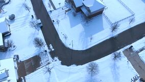 Aerial view of United States Postal Service delivering mail on a cold snowy winter day. Mail truck with mail carrier delivering packages to postal street box stock video footage