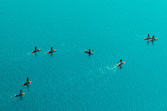 Aerial view of unrecognizable people stand up paddle boarding. Aerial view of unrecognizable group of people stand up paddle boarding on water surface for sport Royalty Free Stock Image