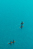 Aerial view of unrecognizable people stand up paddle boarding. Aerial view of unrecognizable group of people stand up paddle boarding on water surface for sport Stock Photography