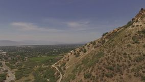 Aerial view of an urban area beyond the peak of a rugged mountain. The camera descends as less of the valley is visible.  Filmed on a hot, summer day with stock footage