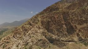 Aerial view of a rugged peak and an urban area in the vast valley below. Aerial view of an urban area beyond a rugged mountain peak.  Filmed on a clear, summer stock footage