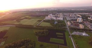 Aerial view of urban landscape with forest. Civilization and nature. Environmentally friendly living. Houses border on forests and fields. at sunset shooting stock video footage