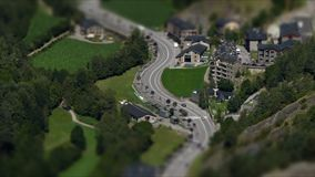 Andorra from above.Time Lapse.Tilt-shift effect,. Aerial view of the  valley bottom of `Ordino` with green meadows and main road traffic  in stock video footage