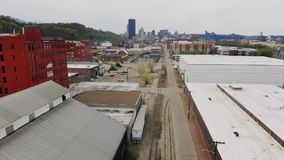 Forward aerial view of industrial warehouses with Pittsburgh skyline in distance stock footage