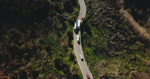 Aerial view of vehicles on a narrow mountain road. Tour bus stops at roadside to let oncoming cars pass. Safety. 4K. Tourism and traveling. Traffic code stock footage