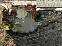 Aerial view with vertical angle of view of an excavation pit filled with liquid soil. Drone shot Royalty Free Stock Photo