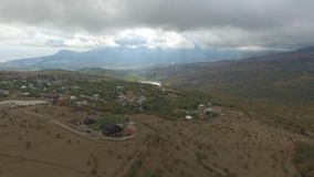 Aerial view of a village in the beautiful clouds and sunlight in front of mountains. Shot. The beautiful mountainous stock video