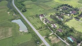Aerial view village near road surrounded by lush fields. Small village near modern asphalt road surrounded by lush fields at pictorial farmland on day aerial stock video