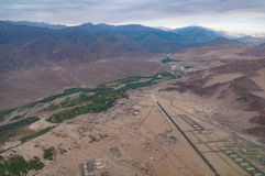Aerial view of village settlement with airport runway in valley surrounded by mountains Stock Photography