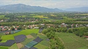 Aerial view villages among fields trees against mountains. Aerial view panoramic approach to villages among green fields trees against mountains and clear blue stock footage