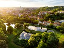 Aerial view of Vilnius cityscape shot from Subaciaus viewpoint on sunset. Clouds reflecting in three ponds of Lithuania capital`s Royalty Free Stock Photo