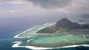 Aerial view on volcanic tropical island. Outer barrier reef surrounding beautiful inner lagoon of the Le Morne Brabant peninsula, UNESCO world heritage site stock footage