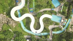 Aerial view water slide in amusement aquapark. People having fun riding on slides in outdoor water park. Summer activity. Aerial view water slide in amusement stock footage