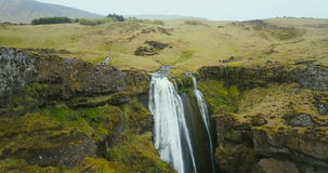 Aerial view of the waterfall Gljufrabui in Iceland. Copter flying over the green valley and river falling down. stock video footage
