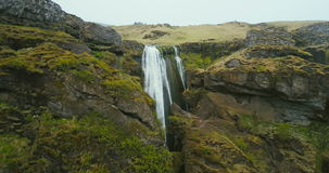 Aerial view of the waterfall Gljufrabui in mountain in Iceland. Copter flying near the turbulent flow falling down. Beautiful scenic landscape of the mountains stock video footage