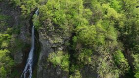 Aerial view. Waterfall on a mountainside overgrown with forests