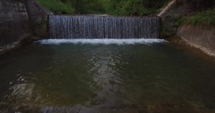 Aerial view of waterfall on a small river on a brink of forest stock video