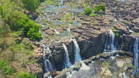 Aerial View Waterfalls from Steep High Cliffs. Aerial view wonderful waterfalls from steep high cliffs among green jungle and clear blue sky stock video footage
