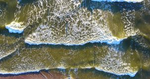 Aerial view waves break on white sand beach at sunset, land meets sea stock video footage