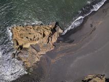 Aerial view of waves crashing on a rock formation. Playa El Golfo. Black beach of the Charco de los Clicos. Lanzarote, Spain. Aerial view of waves crashing on a stock image