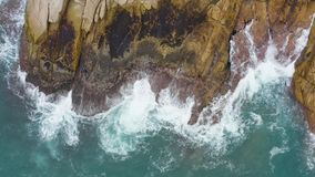 Aerial view of waves crashing on the rocks.  stock footage