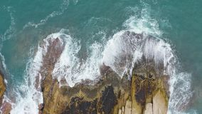 Aerial view of waves crashing on the rocks.  stock video footage