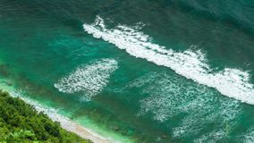 Aerial view of waves rolling one by one to the Nunggalan Beach near Uluwatu, Bali, Indonesia stock footage