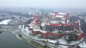 Aerial view of Wawel royal Castle and Cathedral, Vistula River, park, promenade and walking people in winter. Poland stock footage
