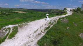 Aerial view of wedding couple having a walk on a cliff above river stock video